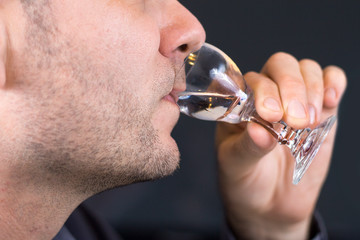 Biały mężczyzna trzyma kieliszek do wódki przystawiony do ust i pije wódkę.