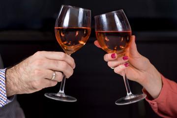 Dłonie kobiety i mężczyzny z kieliszkami do wina w dłoniach wznoszą toast. Kieliszki z winem na ciemnym tle.
