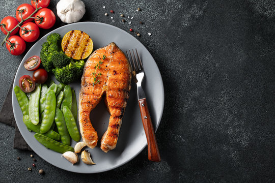 Tasty and healthy salmon steak with green peas, broccoli and tomatoes on a gray plate. Diet food on a dark background with copy space. Top view. Flat lay
