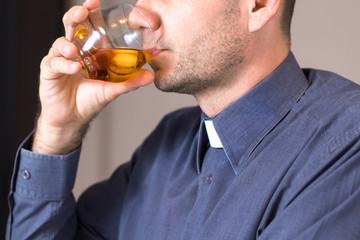 Obraz Ksiądz w koloratce i szarej koszuli pije whisky z lodem ze szklanki. - fototapety do salonu