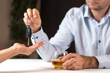 Obraz Piłeś nie jedź. Mężczyzna w jasnej koszuli siedzi przy stole ze szklanką whisky. Oddaje kobiecie kluczyki do auta. - fototapety do salonu