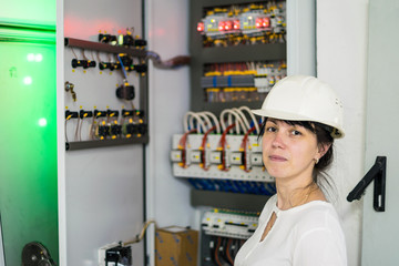 Portrait of an electrician woman in a white helmet next to high-voltage electrical equipment.A girl in an engineering helmet is on the background of a fuse box.