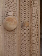 close up of old wooden door wirh three different elaborate detailing