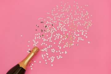 Champagne bottle with confetti stars on pink background. Copy space, top view
