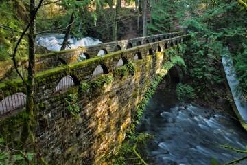 Scenic stone arched bridge over forest stream