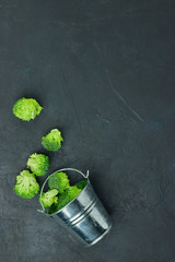 placer green broccoli segments from a small bucket. Healthy eating pattern on dark background. Copy space Top view. Vegetarian food. syroedenie.