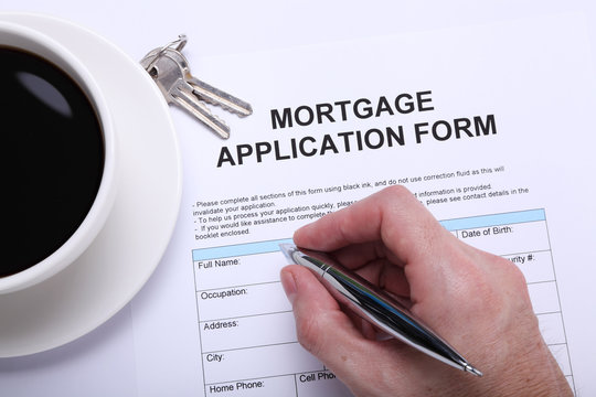 A man filling a home mortgage application form next to a cup of coffee and a couple of keys