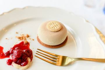 Ice cream dessert with biscuit and red fruit jam elegantly presented with golden cutlery and white background.