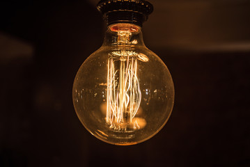 Large long electric incandescent filament in a light bulb glows and reflects warm light.