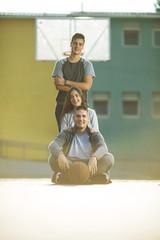 Three teenagers sitting on basketball court