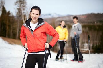 Three friends snowshoeing in park