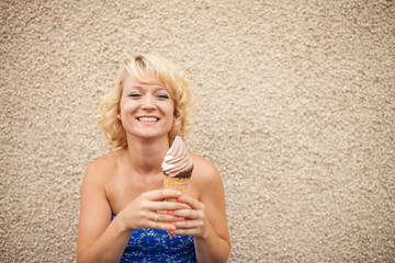 Blonde woman eating ice cream cone dipped in chocolate