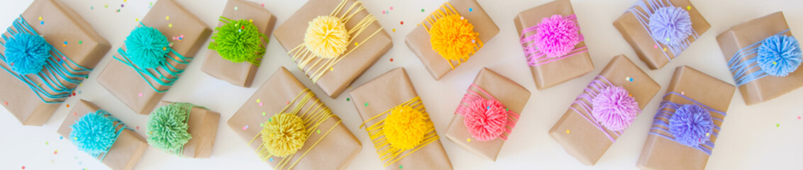 Colored gift boxes with colorful ribbons and pompon. White background. Gifts for Christmas or a birthday.