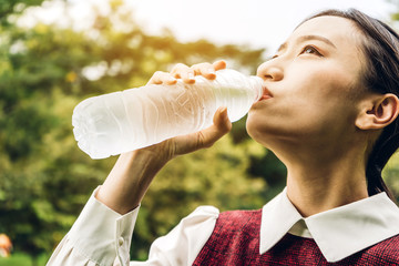Beautiful asia woman drinking water from a bottle while relaxing  and feeling fresh on green natural background at summer green park. Healthy lifestyle concept