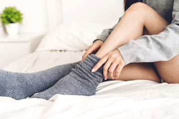 Woman sit on the bed wearing and putting on long warm socks in cold winter day