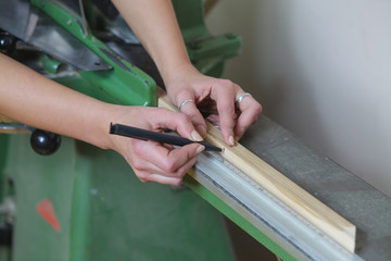 woman worker measuring and marking picture frame wood plank before cutting