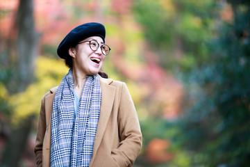 笑顔の女性と紅葉のぼかし背景
