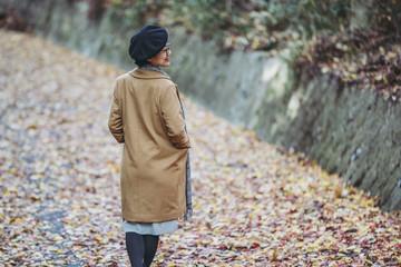 落ち葉の上を歩く女性