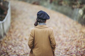 落ち葉の上を歩く女性の後ろ姿