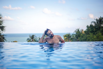 Young attractive sexy Hispanic male, mixed race with beard in the pool, leisure and travel in warm countries
