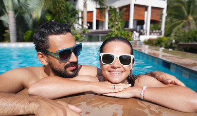 Young attractive couple having fun in the outdoor pool, luxury luxury vacation, real estate in the tropics, honeymoon