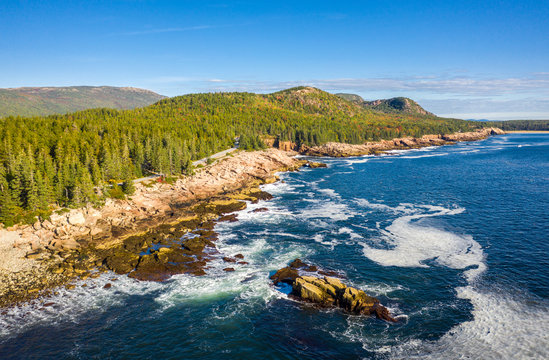 Aerial view of Acadia shore in Maine on a sunny morning with waves crashing on rocky cliffs