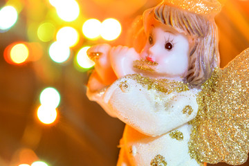 Angel with gold wings on background of bokeh lights. Christmas, New Year picture