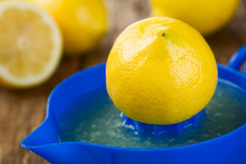 Lemon half on blue lemon or citrus squeezer with lemons in the back, photographed on wood (Selective Focus, Focus on the tip and the front of the lemon half on the squeezer)
