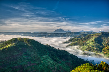 Morning in Uganda with volcanoes in background, fog in the valley and farmlands stretching far