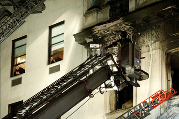People watch from a neighboring building as fire crew work at the site of a fire at the Serbian Mission in New York City