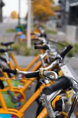 Miet-Fahrräder an einem Fahrrad-Ständer in der Innenstadt mit Fokus auf einen Lenker