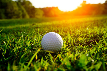 Blurred golf ball on green in beautiful golf course at sunset background. Golf ball on green in golf course at Thailand