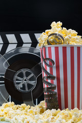 cinema advertising concept: popcorn and film on a dark background