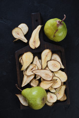 Pear fruit chips and ripe pears over black stone background, above view, vertical shot