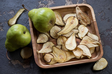 Wooden serving tray with fruit chips made of pear, studio shot on a brown stone background