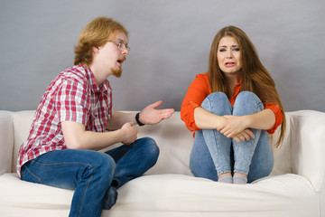 Woman and man after argue on sofa