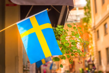 Sweden flag on a street in the Gamla Stan, old town of Stockholm, Sweden.