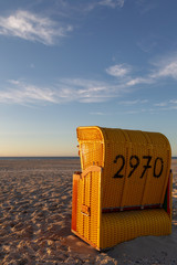 Wall Mural - Beach chair on the East Frisian Island Juist in the North Sea, Germany, in evening light before sunset.