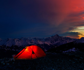 Night bivouac in Mountains, milion star hotel under night sky, red illuminated tent on pass in Alps.
