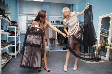 One girl helps the second to choose a dress in a clothing store.