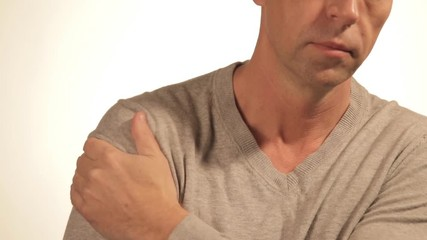 c5a5b2d44227 0 35 Man massages his sore shoulder trying to relieve pain on white  background. Health problems