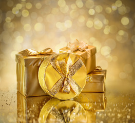 Golden gift boxes as a symbol of wishes and celebration. Golden blurred bokeh background.