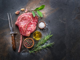 Raw  Rib eye steak or beef steak on the graphite board with herbs and spices.