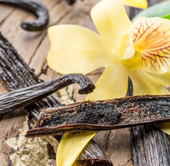 Spoed Fotobehang Kruiderij Dried vanilla fruits and vanilla orchid on wooden table.