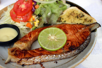 Meal of grilled salmon steak served with salad, slice of lime and sauce dip.