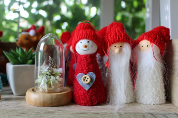 Christmas interior decor: Group of three happy looking knitted snowman and Santa dolls in red bobble hats next to a small terrarium on a window ledge.