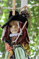 Witch rag doll holding a broomstick