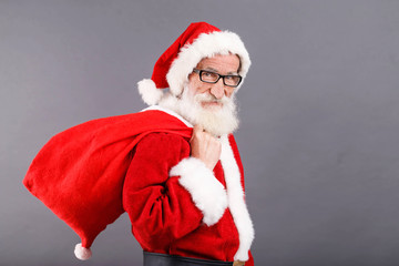 Santa Claus with a white beard wearing glasses and Santa outfit standing with the bag on the gray background, New Year, Christmas, holidays, souvenirs, gifts, shopping, discounts