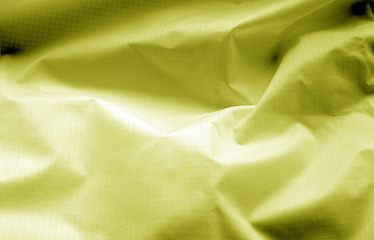 Crumpled transparent plastic surface in yellow color.