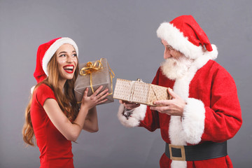 Santa Claus with white beard wearing sungasses and young mrs. Claus wearing Santa hat, red dress and sunglasses standing on the gray background, excited mrs. Santa shakes a gift in silver packaging